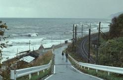 海沿いの街を歩く二人