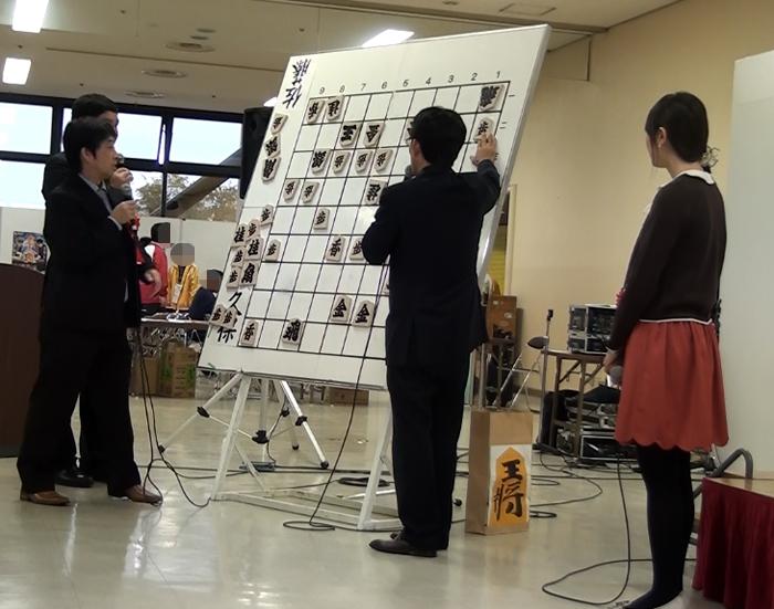 小林六段の言うとおり、駒を手にする佐藤九段