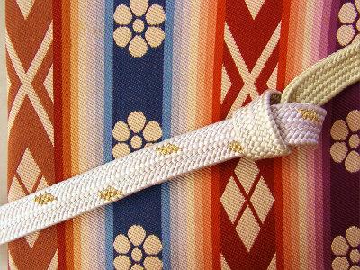 この帯締めの結び目から左は白×金、右はクリーム色です。