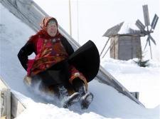 ロシア_「「ユーロビジョン」 注目集める露代表 平均70歳超 おばあちゃんたちの挑戦」03-【写真劇場】チューブに乗り滑り降りて遊ぶガリーナ・コーニェワさんは74歳=3月21日、ロシア連邦・ウドムルト共和国ブラノボ(ロイター)