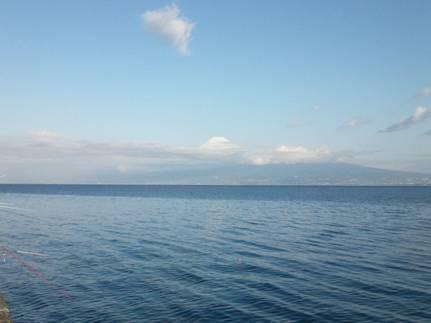 磯釣り現場に雲にかかった富士山を写真撮影